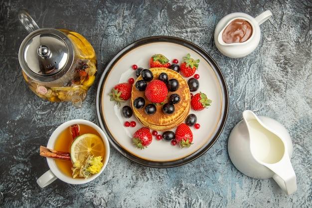 Vista dall'alto gustosi pancake con frutta e tè alla luce
