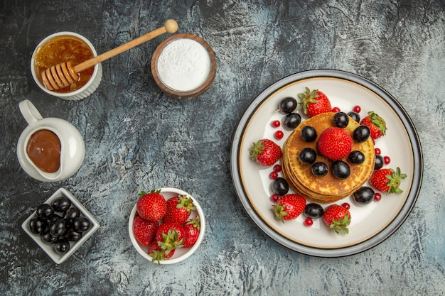 光の上に蜂蜜と果物の上面図おいしいパンケーキ
