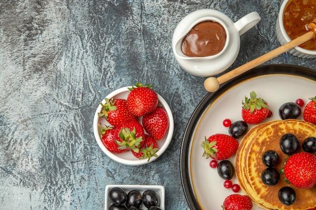 빛에 꿀과 과일을 곁들인 맛있는 팬케이크