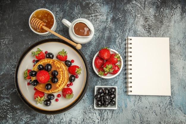 Vista dall'alto deliziose frittelle con miele e frutta su torta di frutta leggera da scrivania dolce
