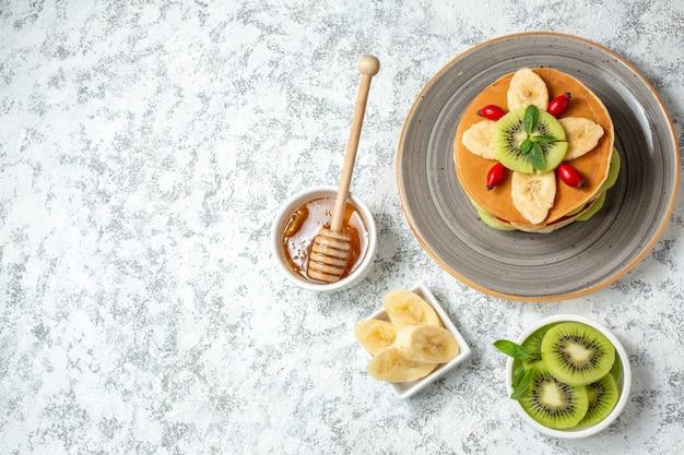 Vista dall'alto deliziose frittelle con miele e frutta a fette su sfondo bianco frutta dolce dessert colazione colore torta zucchero