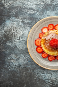 Top view yummy pancakes with honey and strawberries on light