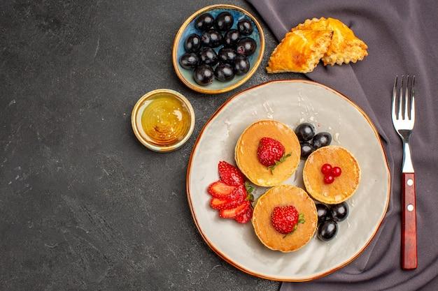 Vista dall'alto gustose frittelle con olive e frutta al buio