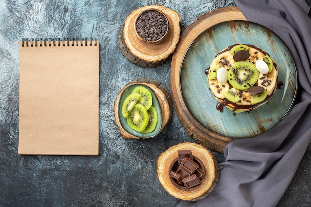 짙은 회색 배경의 달콤한 색상 조식 설탕 과일 케이크 디저트에 얇게 썬 과일과 초콜릿을 곁들인 맛있는 팬케이크