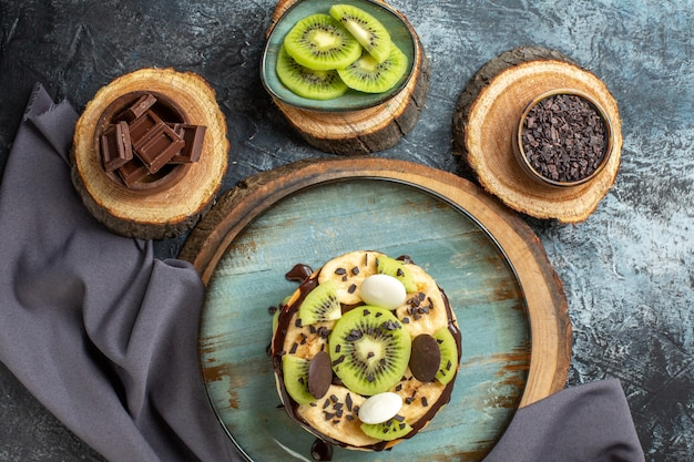 짙은 회색 표면의 달콤한 색상 아침 식사 설탕 케이크 디저트에 얇게 썬 과일과 초콜릿을 곁들인 맛있는 팬케이크