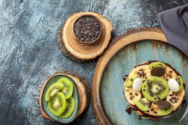 짙은 회색 표면의 달콤한 색상 아침 식사 설탕 과일 디저트에 얇게 썬 과일과 초콜릿을 곁들인 맛있는 팬케이크