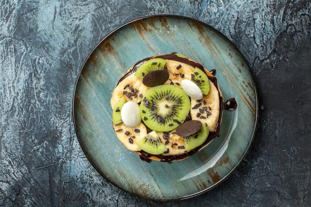 어두운 표면 색상 케이크에 얇게 썬 과일과 초콜릿을 곁들인 맛있는 팬케이크 아침 식사 설탕 과일 달콤한 디저트