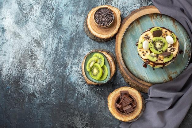 Vista dall'alto gustose frittelle con frutta a fette e cioccolato sulla superficie grigio scuro colore dolce colazione zucchero torta alla frutta dessert