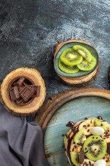 Top view yummy pancakes with sliced fruits and chocolate on the dark-grey surface sweet color breakfast sugar fruit cake dessert