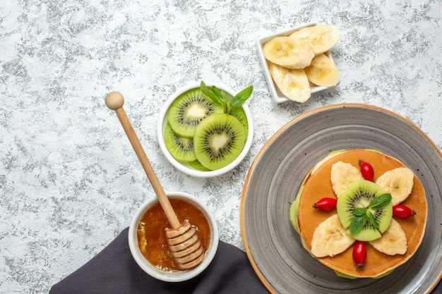 Vista dall'alto gustose frittelle con frutta a fette e miele su superficie bianca frutta dolce dessert zucchero colazione torta colorata Foto Gratuite