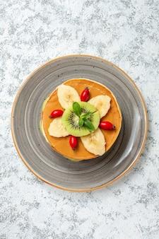 Vista dall'alto gustose frittelle con frutta a fette all'interno del piatto su superficie bianca frutta dolce dessert zucchero colazione torta colorata