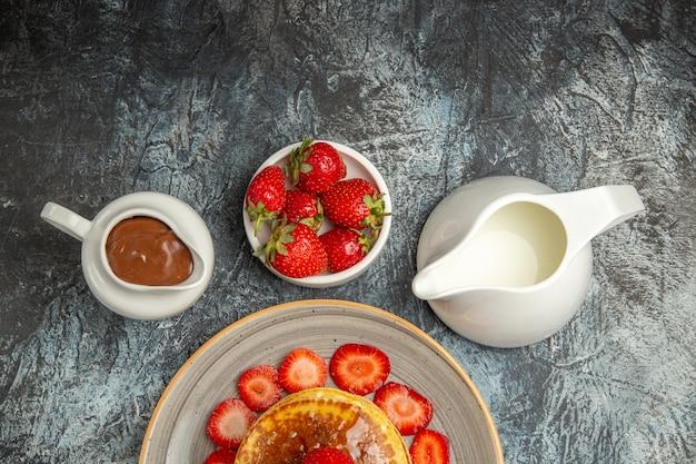 빛에 딸기와 꿀을 곁들인 맛있는 팬케이크