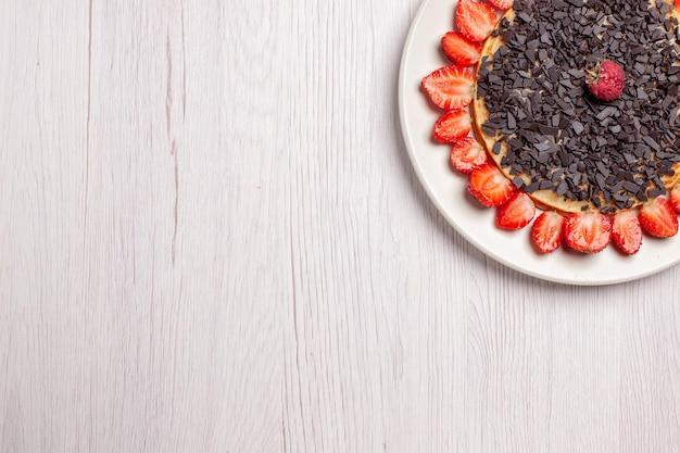 Vista dall'alto di deliziosi pancake con fragole e gocce di cioccolato sul tavolo bianco white