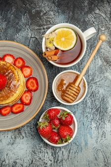Top view yummy pancakes with strawberries and cup of tea on light desk fruit cake sweet
