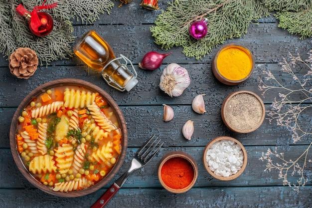 Vista dall'alto gustosa zuppa di pasta dalla pasta italiana a spirale con verdure sul pavimento blu scuro cucina zuppa di pasta cena piatto a colori