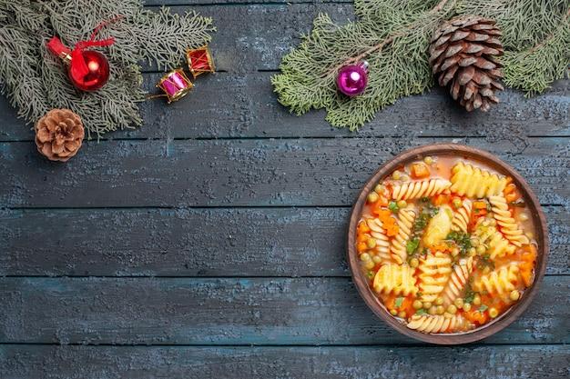 紺色の机の上に緑のスパイラルイタリアンパスタからのトップビューおいしいパスタスープ料理パスタスープカラーディッシュディナー
