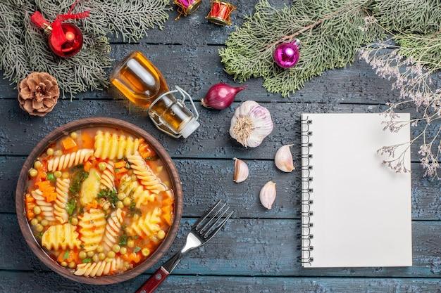 紺色の机の上の緑とスパイラルイタリアンパスタからの上面図おいしいパスタスープ料理パスタスープディナーカラーディッシュ