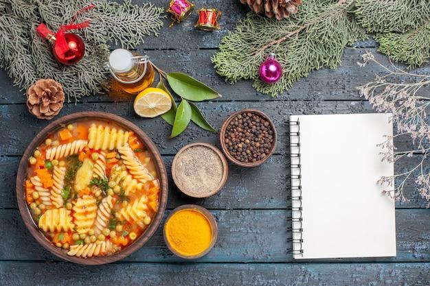 紺色の机の上の緑のスパイラルイタリアンパスタからの上面図おいしいパスタスープ料理パスタスープディナーディッシュカラー