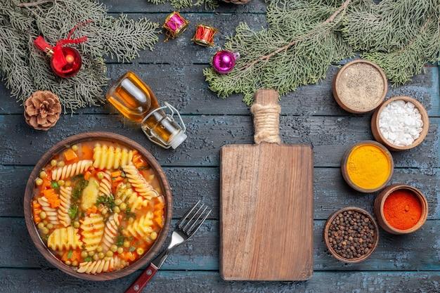 Vista dall'alto gustosa zuppa di pasta dalla pasta italiana a spirale con condimenti sul piatto di colore della cena della zuppa di pasta della cucina della scrivania blu scuro
