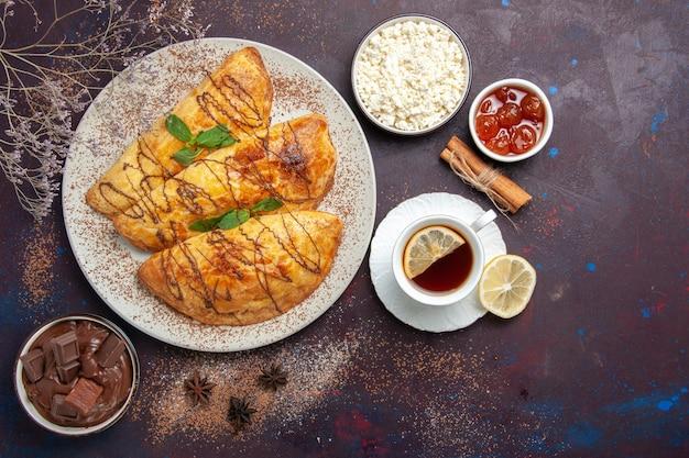 トップビューダークデスクペストリーにお茶とカッテージチーズを添えたおいしいペストリー甘い焼きティーケーキシュガークッキー