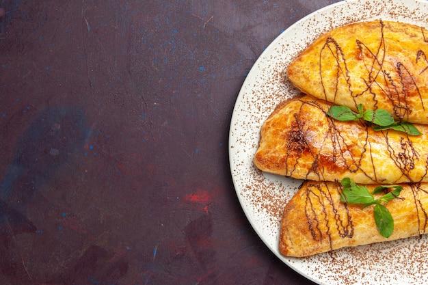暗い背景のプレートの内側にアイシングが付いたおいしいペストリーの上面図ペストリーはビスケットの甘いケーキシュガーを焼く