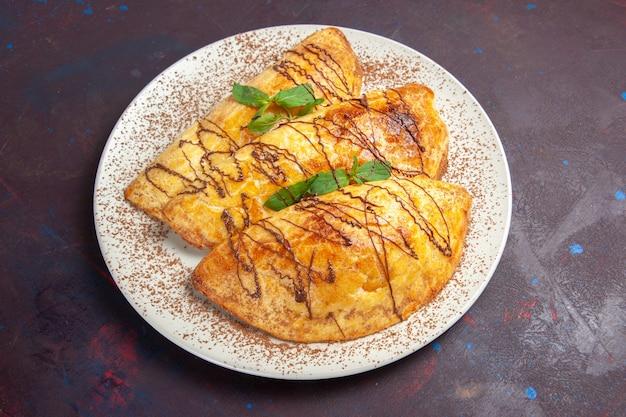 ダークパープルの背景にプレートの内側にアイシングが付いたおいしいペストリーの上面図ペストリーはビスケットの甘いケーキシュガーを焼く