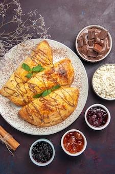 Vista dall'alto squisiti pasticcini con marmellata e ricotta su sfondo scuro pasticceria dolce cuocere tè torta zucchero biscotto