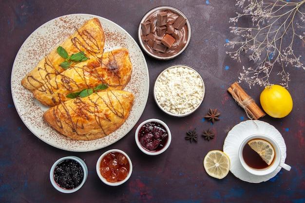 Vista dall'alto squisiti pasticcini con marmellata e ricotta su sfondo viola scuro pasticceria dolce cuocere tè torta zucchero biscotto
