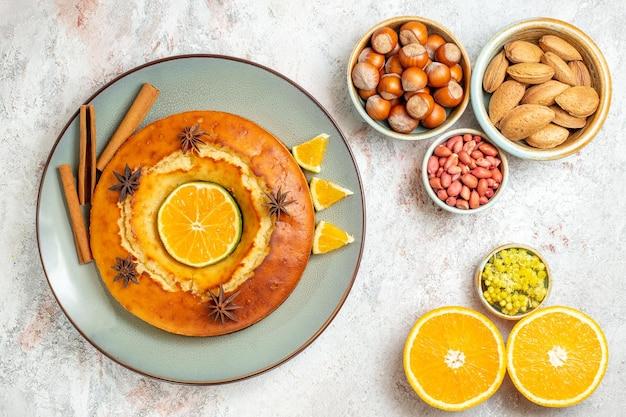 トップビューおいしいパイおいしいデザートナッツとオレンジの白い背景の上のお茶ケーキパイティービスケット甘いデザートフルーツ