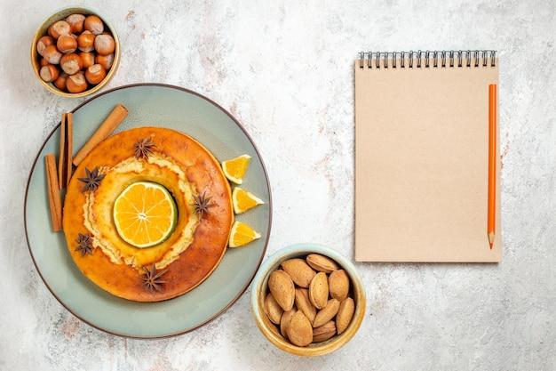 上面図白い背景にオレンジスライスとお茶のためのおいしいパイおいしいデザートフルーツケーキパイティービスケット甘いデザート