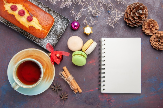 Top view yummy pie with macarons and cup of tea on dark surface cake sugar cookie pie sweet biscuit tea