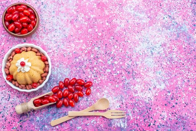 Вид сверху вкусный простой торт со сливками и свежим арахисом вместе со свежим красным кизилом на ярком светлом настольном пироге, бисквитном сладком орехе и ягодах