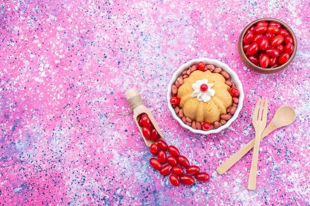 Вид сверху вкусный простой торт со сливками и свежим арахисом вместе со свежим красным кизилом на ярком свете настольного торта, бисквитного сладкого ореха
