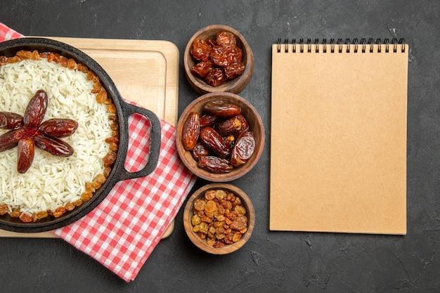 Vista dall'alto gustoso piatto di riso cotto plov con uvetta diversa sullo sfondo scuro piatto di uvetta cibo olio per cena di riso