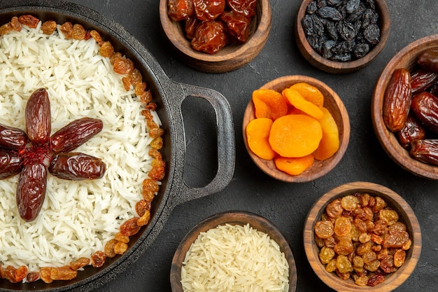 Vista dall'alto gustoso piatto di riso cotto plov con uvetta diversa su sfondo scuro riso all'uvetta cena olio frutta orientale piatto secco