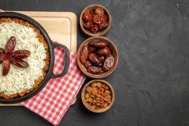 Vista dall'alto yummy plov piatto di riso cotto con uvetta diversa su sfondo scuro piatto di riso all'uvetta cibo olio per cena