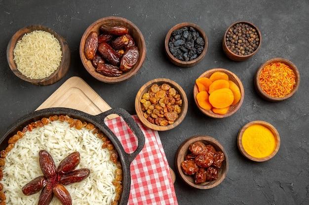 Vista dall'alto gustoso piatto di riso cotto plov con uvetta diversa sul pavimento scuro piatto di uvetta cibo olio per cena di riso