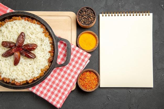 Vista dall'alto yummy plov piatto di riso cotto con uvetta su sfondo scuro uvetta piatto di riso cibo olio per cena