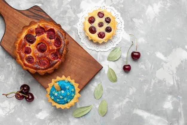 明るい背景のケーキと新鮮なサワーチェリーとフルーツパイを焼くおいしいラズベリーケーキの上面図