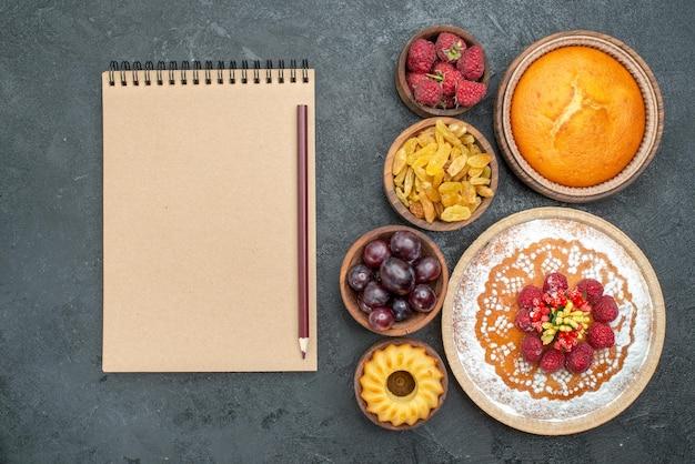 上面図灰色の表面にレーズンとフルーツが入ったおいしいラズベリーケーキパイティービスケットケーキクッキースウィート