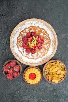 Вид сверху вкусный малиновый торт с изюмом на серой поверхности бисквитный чай сладкий пирог торт сахар