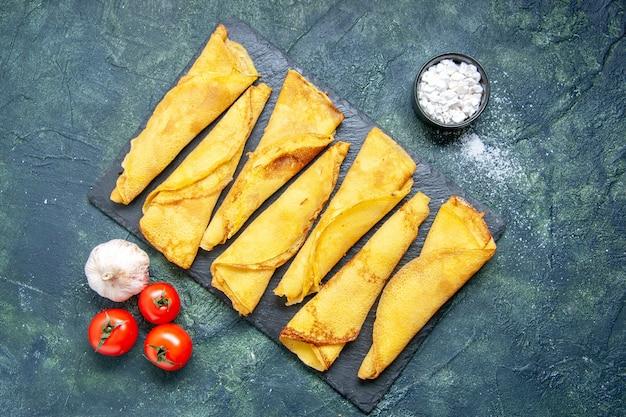 Vista dall'alto deliziose frittelle arrotolate allineate su sfondo scuro pasta hotcake farina colorata pasticceria torta torta dolce carne