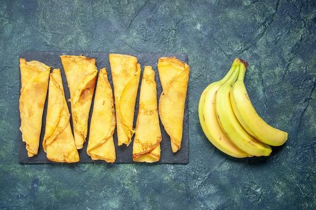 Vista dall'alto deliziose frittelle arrotolate con banane su sfondo scuro pasta per torta hotcake farina colorata pasticceria carne di torta