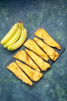 Vista dall'alto deliziose frittelle arrotolate con banane su sfondo scuro pasta per torta pasto per hotcake pasticceria torta dolce carne