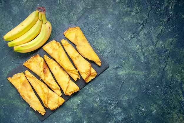 上面図暗い背景にバナナとおいしいロールパンケーキケーキ生地ホットケーキカラーミールペストリー甘いパイ肉の空きスペース