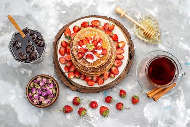 Una vista dall'alto gustose frittelle rotonde con tè alla crema e fragole rosse sulla torta della scrivania in legno