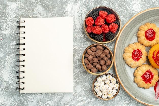 Вид сверху вкусное песочное печенье с печеньем и конфетами на белом