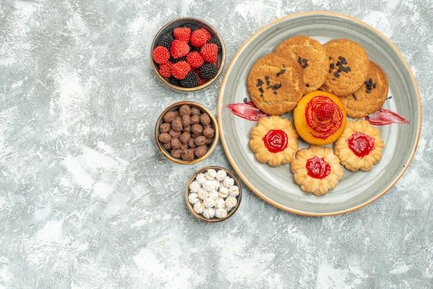 白の上のクッキーとキャンディーとおいしい砂のビスケットの上面図