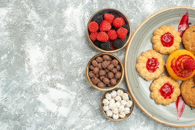 Vista dall'alto deliziosi biscotti di sabbia con biscotti e caramelle su bianco chiaro