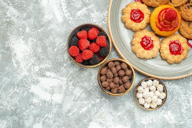 Vista dall'alto squisiti biscotti di sabbia con biscotti e caramelle su bianco